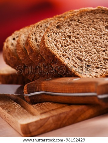 close-cut slices of rye bread on wooden cutting board, sharp knife next, all on kitchen table - stock photo