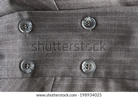 Close detail of a button on a pin striped business suit - stock photo