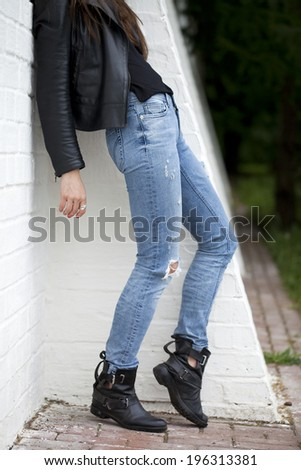 Close female blue jeans on white brick wall