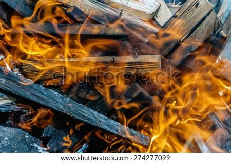 Close fire in fireplace with burning wood, close up - stock photo