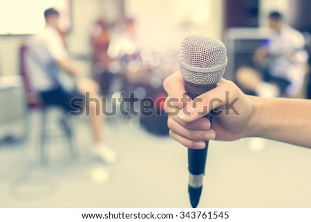 close hand holding a microphone on musician blurred background on retro style - stock photo