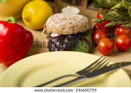 Close Healthy Burger with Leafy Veggies Beside Fresh Ingredients and Plate with Fork and Knife - stock photo
