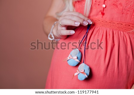 Close image of pregnant woman with boots - stock photo