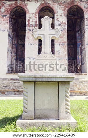 close image of stone cross in front of painted church wall in Moldovita Monastery, Bucovina, Romania