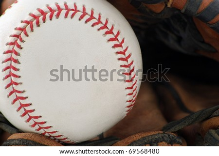 close of a baseball in the glove
