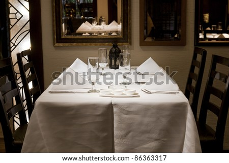 close of a dining table in a restaurant with white napkins and wine glasses. - stock photo