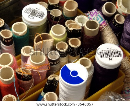 close of box full of  reels of threads from above - stock photo