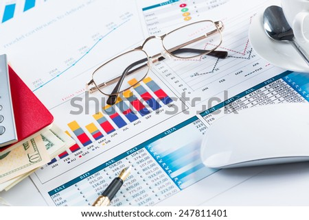 Close of business workplace with financial reports and office stuff