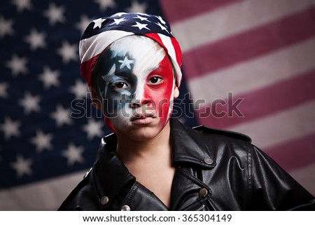 Close of of a young, mixed race boy wearing red, white and blue face make up and standing in front of an American Flag.