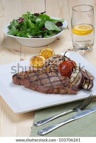 Close of of one piece cut of medium rare grilled steak with spicy herb sauce, garnished with grilled vegetables and organic brown rice.