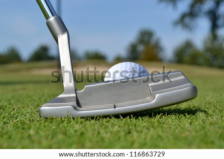 close of putter and golf ball on green - stock photo