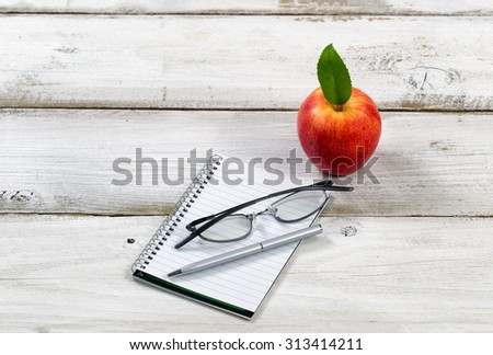 Close of simple writing and reading objects with apple on rustic white wood.  - stock photo