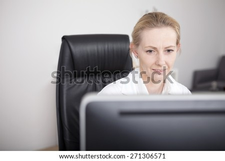 Close p Adult Female Doctor Sitting at her Worktable and Looking at her Computer Screen Seriously. - stock photo