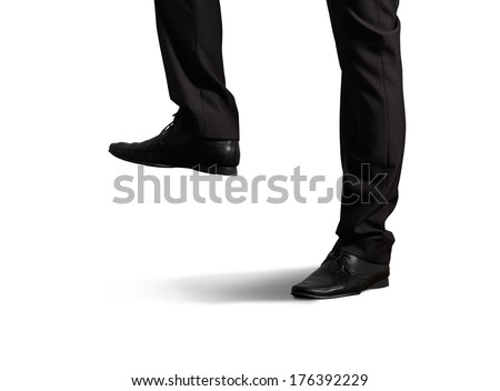 close photo of male legs in black trousers and shoes. isolated on white background