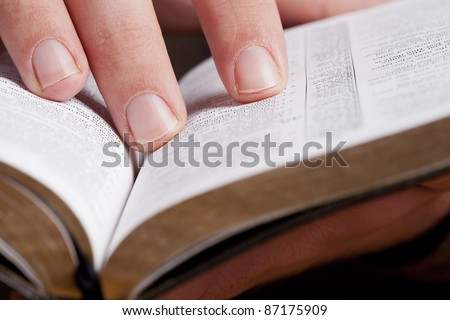 Close photo of man thumbing through the Bible. Macro. - stock photo