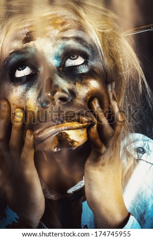 Close picture of a scary female zombie pulling funny face while looking up the light shining from above