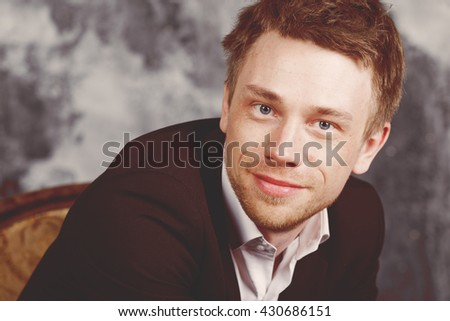 Close portrait of a beautiful imposing man. Blond. Dressed in a classic formal suit. smiling and kindly.