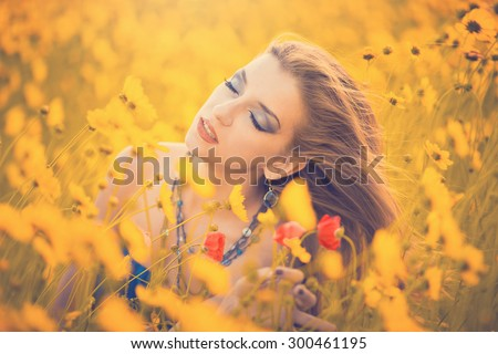 Close portrait of a beautiful young girl in the middle of the field among the wildflowers in the summer at sunset