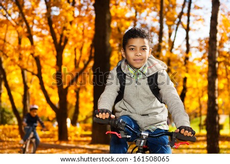Close portrait of a boy on the bicycle riding in autumn park with orange leaves - stock photo
