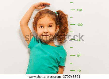 Close portrait of a girl show height on wall scale - stock photo
