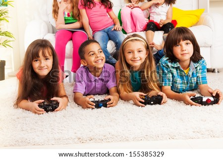 Close portrait of a group of diversity looking kids, boys and girls playing videogame, laying on the floor in kids room - stock photo