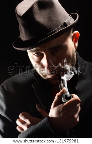 close portrait of a pipe smoker on a black background