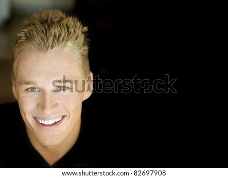 Close portrait of a sexy smiling male model against dark background with copy space - stock photo