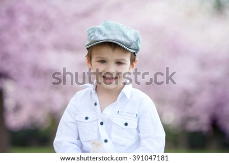 Close portrait of adorable little caucasian boy in a cherry tree blooming garden in the afternoon, drinking smoothie - stock photo