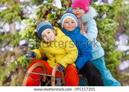 Close portrait of boys and girls on sledge  - stock photo