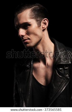 close portrait of confident biker in black leather jacket posing in dark studio background looking away - stock photo