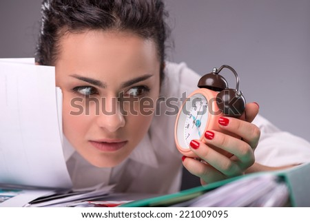 Close-portrait of confused girl sitting at the table with a pile of documents and looking with a fright at a clock, isolated on grey background with copy place, concept of time management at work - stock photo