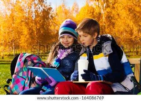 Close portrait of couple children, boy and girl sitting on the bench in autumn park reading textbook and drinking - stock photo