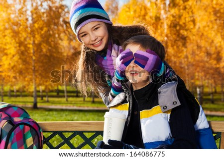 Close portrait of couple children, girl covers boys face with palms and laughing making a surprise, guy sitting on the bench in autumn park - stock photo
