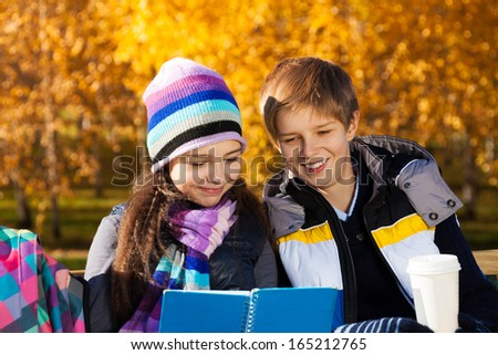 Close portrait of couple children reading textbook with smile on the, boy and girl sitting on the bench in autumn park wearing warm clothes - stock photo