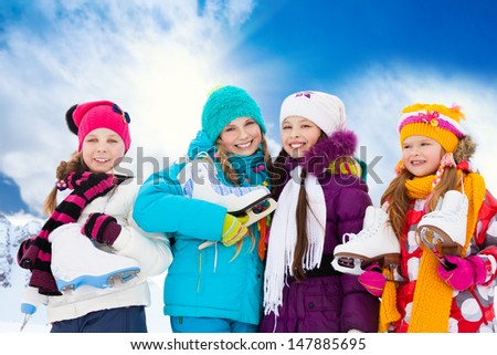 Close portrait of group of four happy smiling Caucasian girls friends standing outside with ice-skates - stock photo