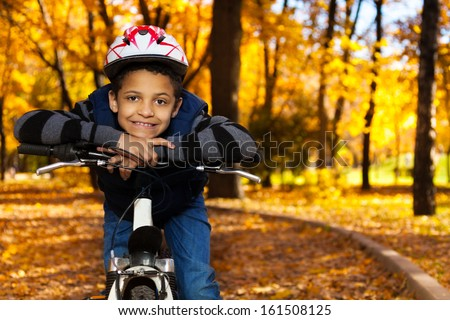 Close portrait of happy smiling 8 years old black boy riding a bike in the autumn park leaning on bicycle stern - stock photo