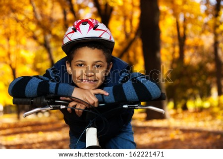 Close portrait of happy smiling 8 years old black boy riding a bike in the autumn park leaning on bicycle stern wearing helmet - stock photo