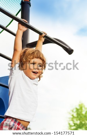 Close portrait of happy three years old boy about to hand on the horizontal bar on playground - stock photo