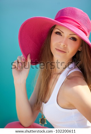 Close portrait of pretty cheerful woman wearing white dress and straw pink hat in sunny warm weather day near the sea - stock photo