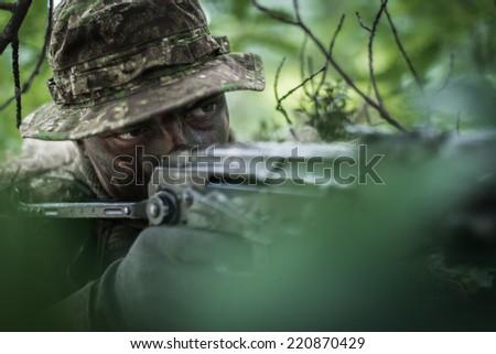 close portrait of rebel hidden between leaves - stock photo