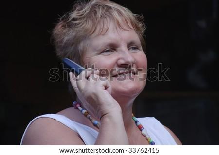 close portrait of senior lady on phone smiling - stock photo
