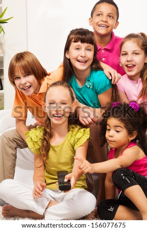 Close portrait of smiling happy girl with her friends sitting on the sofa switch on TV with remote control - stock photo