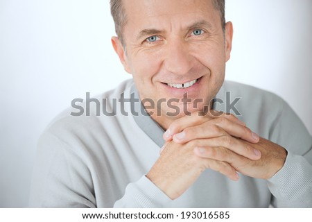 Close portrait of smiling middle aged businessman with hands - stock photo
