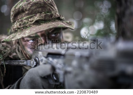 close portrait of special forces soldier wearing boonie hat, aiming with machine gun. - stock photo