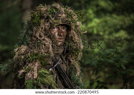 close portrait of the soldier wearing ghillie suit, face painted with camouflage paints - stock photo