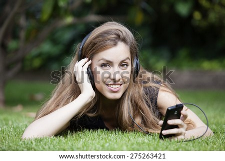 Close portrait of young beautiful smiling woman in headphones outdoors in summer - stock photo