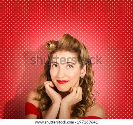 Close portrait on the face of a beautiful young pinup fashion woman wearing retro make-up and classic 50s hairstyle looking up to beauty copyspace. Red polka dot studio background - stock photo