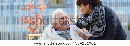 Close relationship between grandfather in wheelchair and granddaughter - stock photo