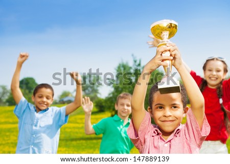 Close shoot of black happy smiling little boy holding prize cup with group of boys and girls on background - stock photo
