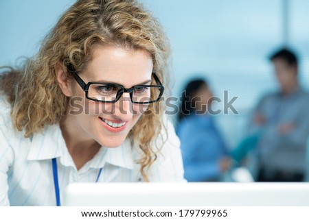 Close shot of a businesswoman having seen the interesting news in the Internet on the foreground  - stock photo